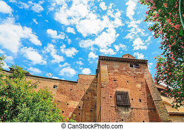 antique brick wall under a cloudy sky in Siena