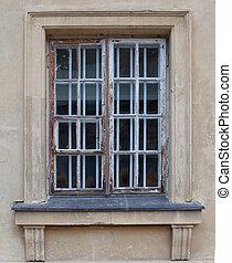 Antique broken wooden window on old brick building with green decrepit ornamented facade.