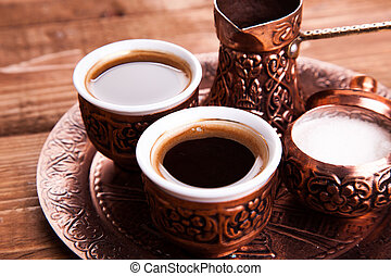 Antique bronze pitcher and coffee cup set with dates in a tray isolated on a white background, Turkish coffee set on wooden background.