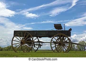 Antique buckboard sky background in open field