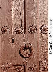 Antique classic doorknob on a brown painted wooden door.