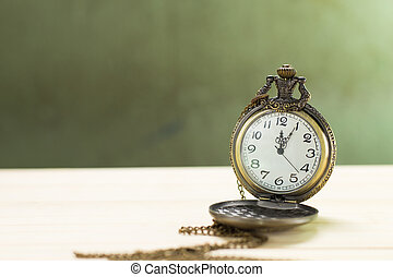 Antique clock on the wooden floor and green wall Background.