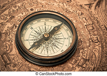 Antique compass lying on old style map. Sepia toned.