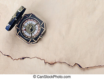 Antique compass over old paper background