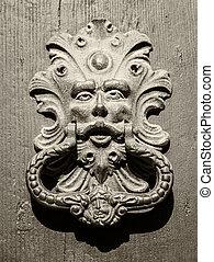 Antique door knocker of an old door in Italy.