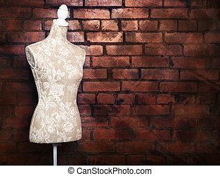 Antique dress form with vintage look against brick background