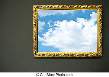 Antique empty golden frame on grunge wall with sky photograph