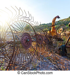 Old hay rake at sunrise, Italy