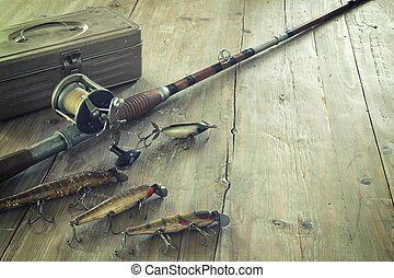 Antique Fishing Rod and Lures on a Grunge Wood Surface - ...