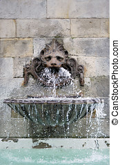 Antique fountain in a wall. Water is flowing from the mask
