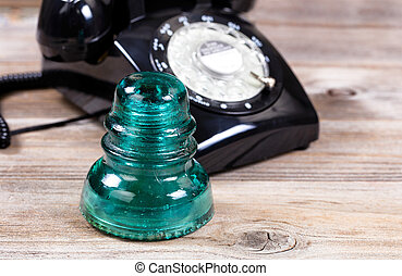 Antique glass insulator and rotary dial phone on rustic wooden boards