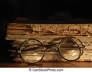 Antique glasses on old weathered book.