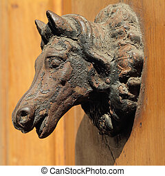 antique horse head on the door in Tuscany, Italy