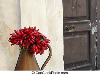 Antique jug with bunch of red peppers against old wall, shallow dof