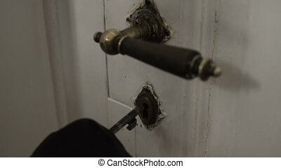 Close up shot of an anonymous gloved hand inserting an old key into an antique door latch and opening the door to get entry to the passageway.
