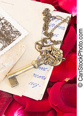 Antique Key with old papers and rose petals