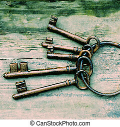 Antique keys - Antique copper keys on old wooden background,...