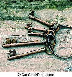 Antique keys - Antique copper keys on old wooden background,...