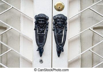 Antique knocker on a vintage wooden white door. Architecture in St. Julian, Malta.
