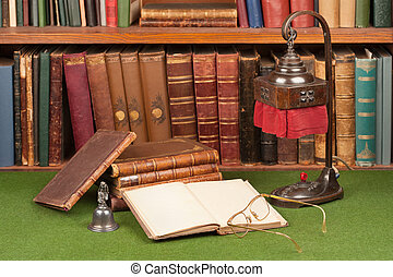 Antique leather books, lamp and reading glasses on green ...