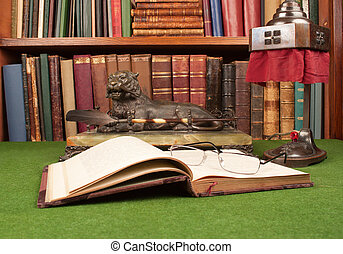 Antique leather books, lamp and reading glasses on green blotter.