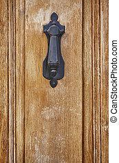 Antique metallic doorknob on a vintage wooden door. Decoration