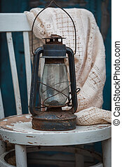 Antique oil lamp on the rustic white chair