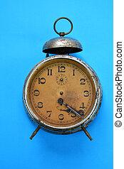 Antique old grunge alarm-clock on blue