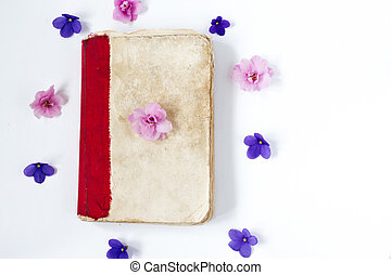 antique paper book and flowers on white background .
