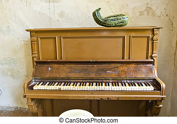 antique piano and green zucchini courgette in old manor room...