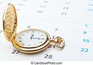 Antique pocket watch on a calendar.
