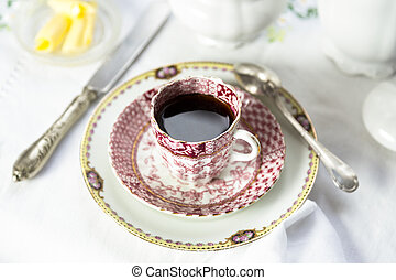 Antique porcelain breakfast setting with black coffee