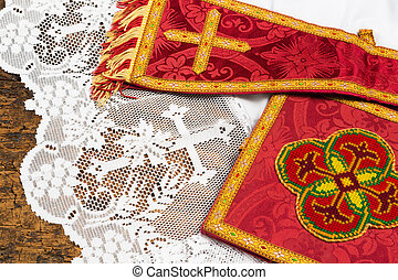 Antique red damask chalice veil and maniple on a white lace catholic priest surplice