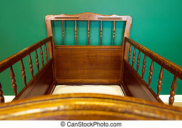Antique retro wooden baby crib in babies room with green walls modern interior
