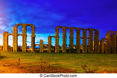 antique Roman Aqueduct of Merida in evening lights. ...