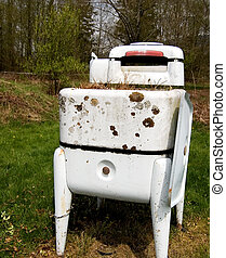 This is a photo of an antique wringer washer that's rustic and showing it's age.