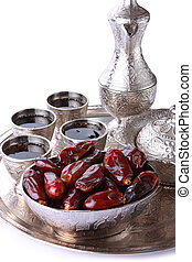 Antique silver pitcher and coffee cup set with dates in a tray isolated on a white background - vertical. Including clipping path.