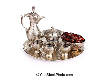Antique silver pitcher and coffee cup set with dates in a tray isolated on a white background. Including clipping path.
