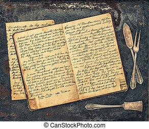 Antique silverware and vintage handwritten recipe book