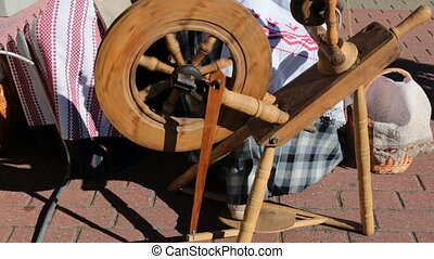 Antique spinning wheel in use - A woman in traditional...