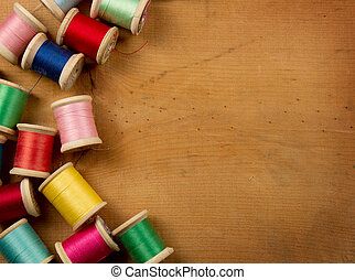 Antique spools of thread multicolored on a wooden background, room for copy space.