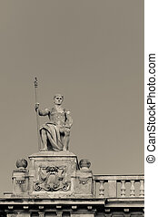 Antique statue sitting on a building in Budapest, Hungary