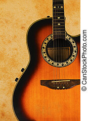 Antique textured vintage warm toned image of an acoustic guitar on a retro background.