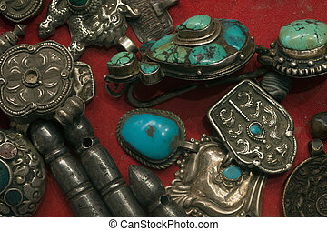 Antique Tibetan silver man's ornaments: the men's earrings with turquoise, amulets, Buddhist knives.