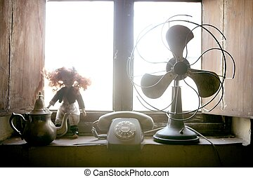 Antique vintage air fan, doll and phone at the window...