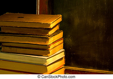 Antique, vintage, old books sitting on ledge of olf antique black, chalk board at school