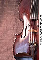 Antique violin closeup against gray fabric background vertical