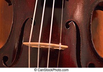 Antique violin closeup against wood
