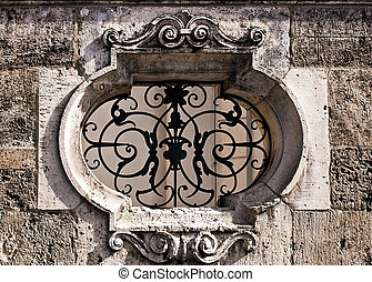 decorated marble frame closed by iron decorated grille on stone wall