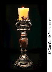 Antique wooden candlestick isolated on black background